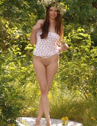 Admirable teen bombshell with a wreath on her pretty head undressing in the forest glade.