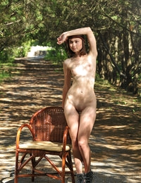 Delicious dark haired sweetie undressing and posing naked outdoor on the chair in the park.