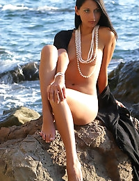 Laila in pearls on rocky shore.