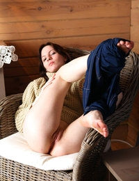 Tinka removes jeans in her comfy chair and shows tits under sweater