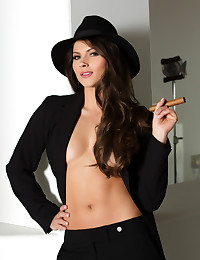 Aspen Rae smokes a cigar while taking off her hat and jacket.