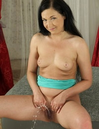 Pretty raven haired girl pours pee on herself