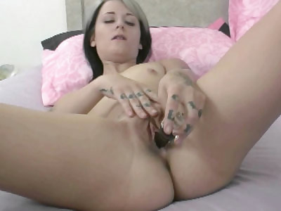 Raunchy college girl Samus Andrews shows off her tattoos while she fucks her big glass dildo