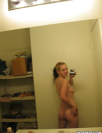 Cute blonde gets naked and  takes selfshot mirror pictures of her pierced nipples
