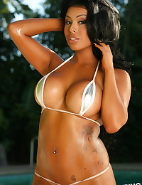 Busty Alluring Vixen Glori is poolside in a very skimpy tear drop string bikini that barely covers her perfect curves