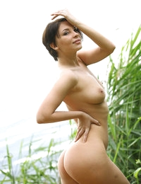 Short-haired seductress Cecelia looks capturing getting nude by water