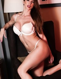 Courtney Shane posing on a chair in white lingerie