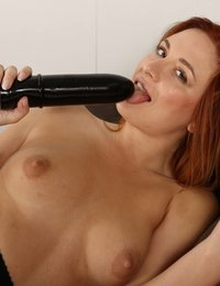 Cute redhead in stockings fucks a big black toy